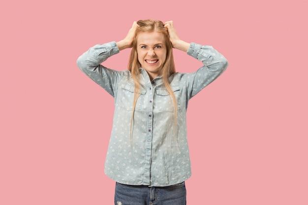 Portret van een boze vrouw die camera bekijkt dat op een roze achtergrond wordt geïsoleerd