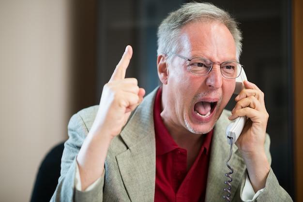 Portret van een boze zakenman die bij telefoon schreeuwt
