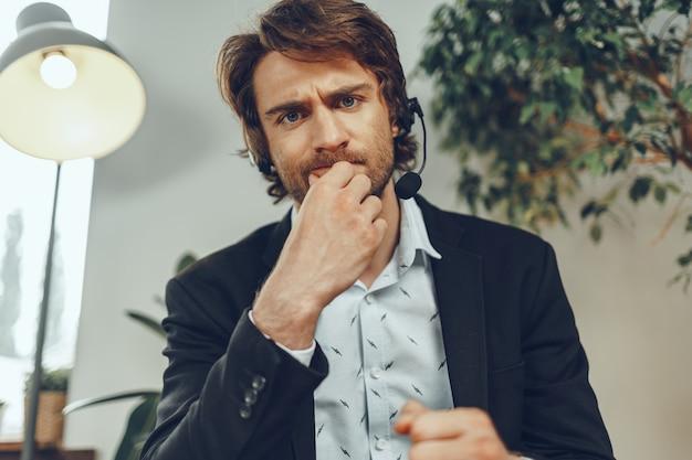 Portret van een boze zakenman met hoofdtelefoon met stressvol online gesprek close-up