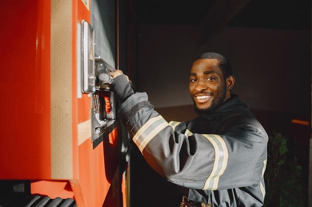 Portret van een brandweerman die zich voor een brandweerwagen bevindt