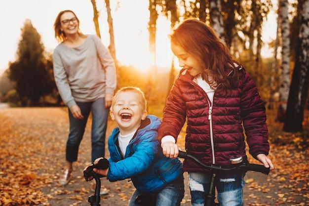Portret van een broer en zus spelen met hun fietsen buiten tegen zonsondergang lachen.