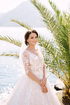 Portret van een bruid in een crème jurk onder een palmboom op een achtergrond van de zee fineart bruiloft