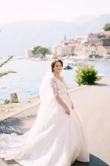 Portret van een bruid in een crèmekleurige jurk onder een palmboom