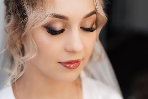Portret van een bruid in een schoonheidssalon, mooie blonde met haar en make-up in een sluier.