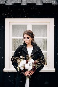 Portret van een bruid in een witte zijden trouwjurk en een zwarte jas met een bruidenboeket in haar handen