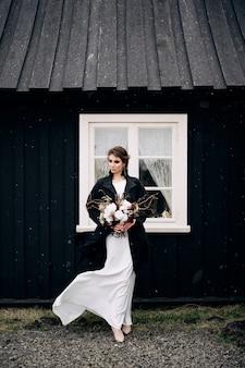 Portret van een bruid in een witte zijden trouwjurk en een zwarte jas met een bruidenboeket