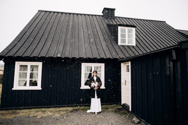 Portret van een bruid in een witte zijden trouwjurk en een zwarte jas met een bruidsboeket in haar