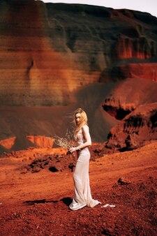 Portret van een bruid model in een gouden bruiloft avondjurk in een geelrode zandgroeve in de