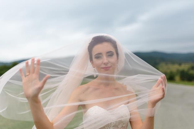 Portret van een bruid onder een sluier. de wind blaast een sluier op. detailopname.