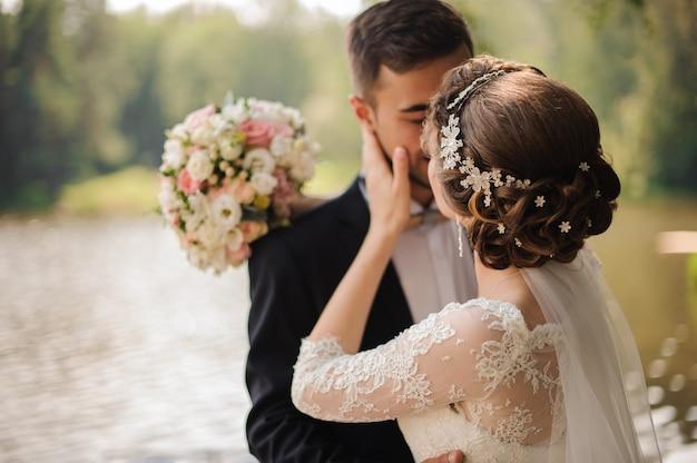 Portret van een bruidegom die een bruid kust