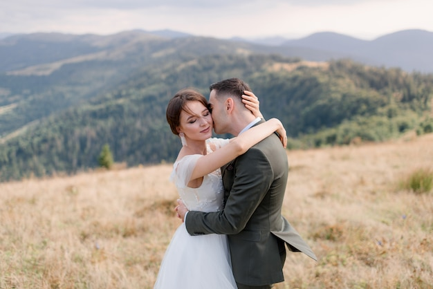 Portret van een bruidegom en een bruid alleen in de prachtige bergen op de zonnige zomerdag