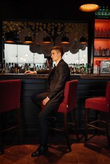 Portret van een bruidegom zittend op een stoel bij de bar. low key.