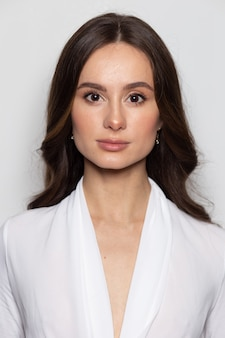 Portret van een brunette blanke vrouw die de normen van een officiële pasfoto bereikt.