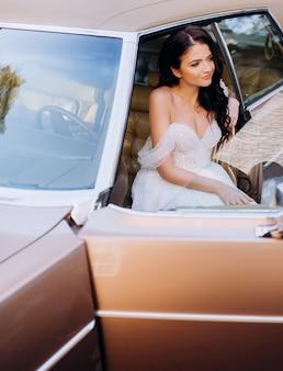 Portret van een brunette bruid die op de voorbank van een roze retro-auto zit