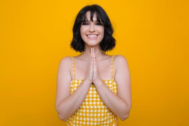 Portret van een brunette gekleed in witte jurk show alsjeblieft met handen kijken camera lachend tegen een gele studio muur.