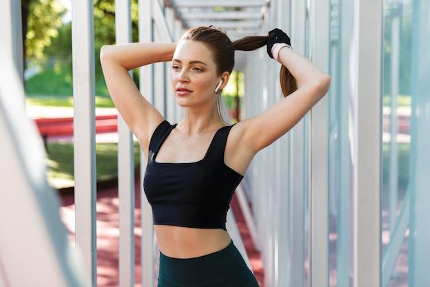 Portret van een brunette jonge vrouw die een trainingspak draagt dat aan het trainen is met een horizontale metalen staaf op een sportveld in een groen park