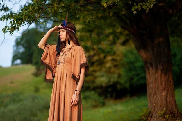 Portret van een brunette jonge vrouw in inheemse boho jurk kant kijken