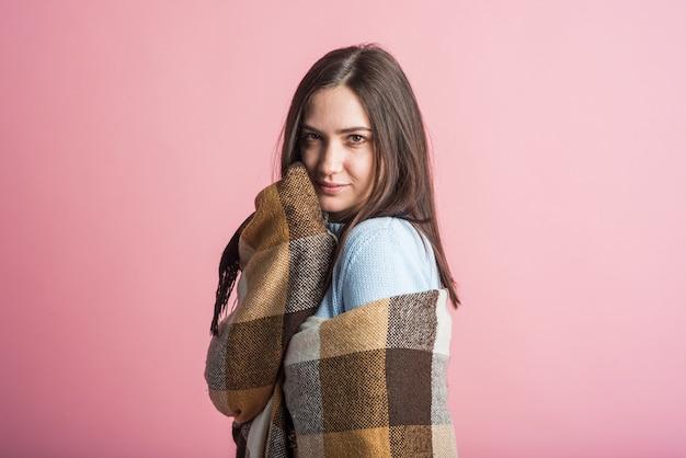 Portret van een brunette meisje dat is verpakt in een deken in de studio op een roze achtergrond
