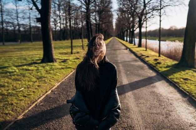 Portret van een brunette meisje met plezier in een park in de stralen van de felle zon.