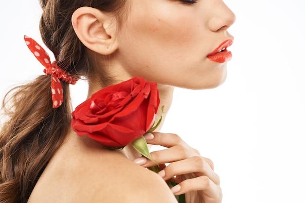 Portret van een brunette met rode lippenstift op haar lippen, mooie vrouw in glazen met een roos