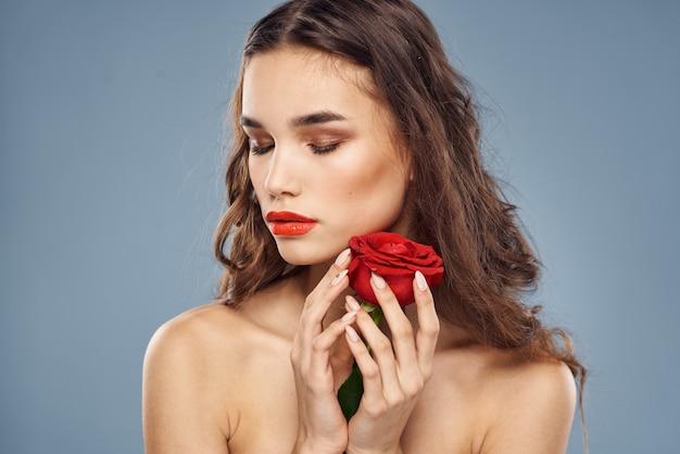 Portret van een brunette met rode lippenstift op haar lippen, mooie vrouw met een roos