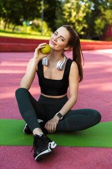 Portret van een brunette, sportieve vrouw met een trainingspak die lacht en een groene appel vasthoudt terwijl ze op een fitnessmat in een groen park zit