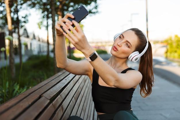 Portret van een brunette sportvrouw die een trainingspak draagt in een koptelefoon die selfie neemt portret op een smartphone terwijl ze op een bankje in het stadspark zit