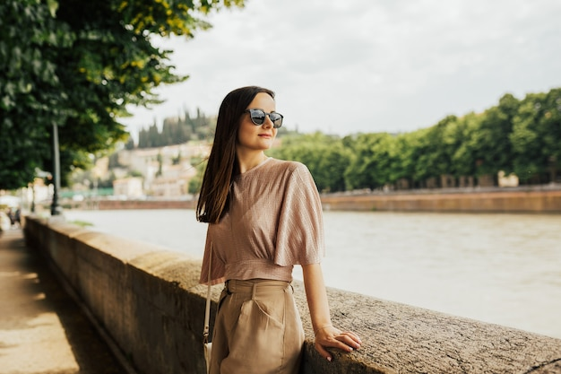 Portret van een brunette stijlvolle vrouw zittend op het stenen hek bij de rivier in de stad verona, italië.