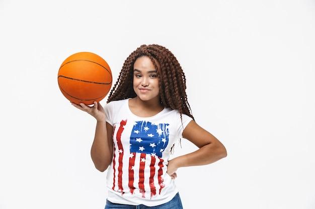 Portret van een brunette vrouw die zich verheugt en basketbal vasthoudt tijdens het spel terwijl ze geïsoleerd tegen een witte muur staat