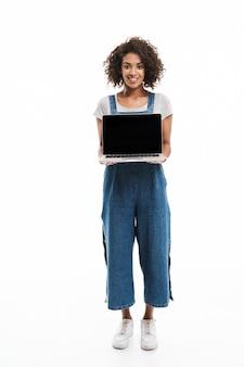 Portret van een brunette vrouw gekleed in een denim overall glimlachend en met een opengeklapte laptop geïsoleerd over een witte muur