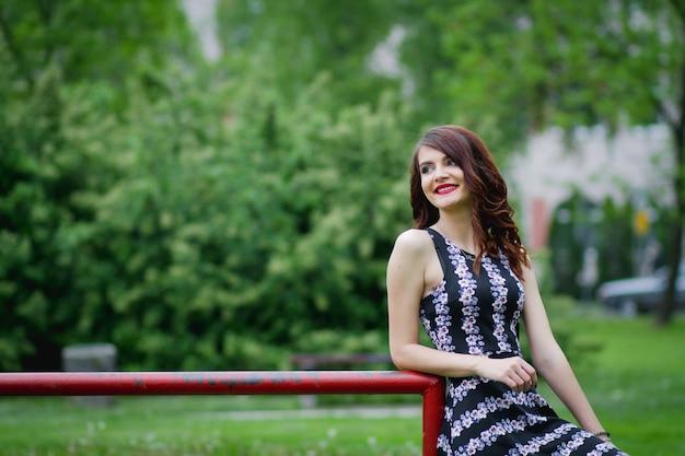 Portret van een brunette vrouw in een gebloemde jurk poseren in een park