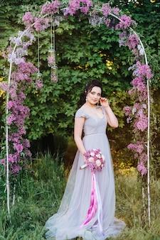Portret van een brunette vrouw in een lentetuin van seringen voor de huwelijksceremonie op de boog
