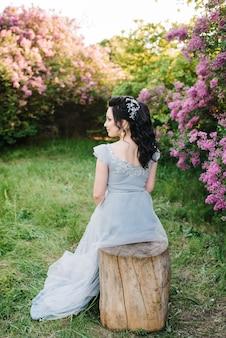 Portret van een brunette vrouw in een lila lentetuin voor de huwelijksceremonie