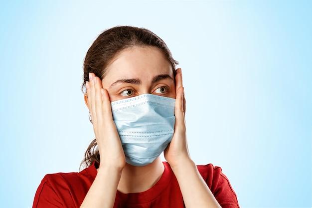Portret van een brunette vrouw in een medisch masker en een rood t-shirt