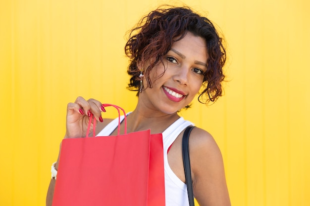 Portret van een brunette vrouw met een boodschappentas op een gele muur.