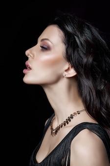 Portret van een brunette vrouw met een chique kapsel en een ketting om haar nek, sieraden. natuurlijke cosmetica en mooie lichte make-up op het gezicht van het meisje