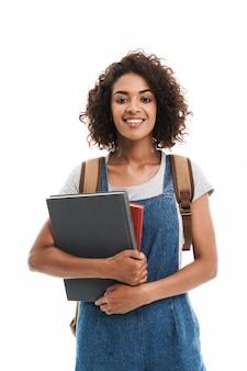 Portret van een brunette vrouw met een rugzak die lacht en oefenboeken vasthoudt die over een witte muur worden geïsoleerd
