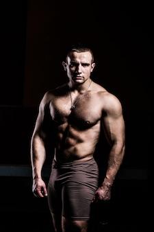 Portret van een brutale bodybuilder op een zwarte achtergrond