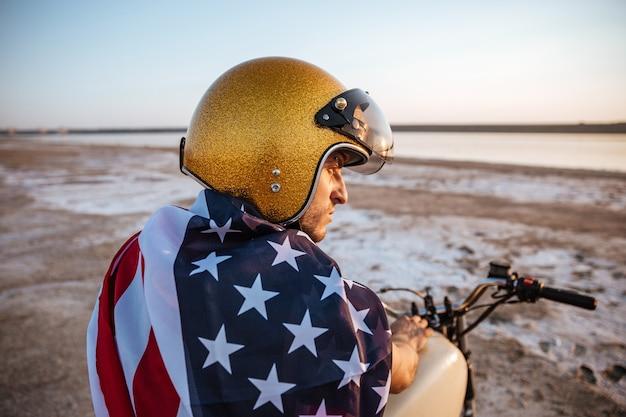 Portret van een brutale man met gouden helm en amerikaanse vlag zittend op de motorfiets close-up