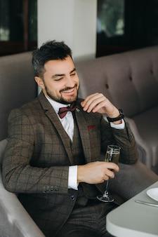 Portret van een brutale zelfverzekerde man in een pak, lachend met een glas. een glas champagne in de hand van een brutale zakenman