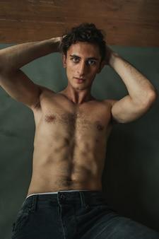 Portret van een brute topless man met krullend haar op de vloer.