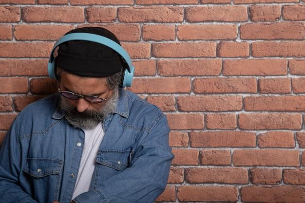 Portret van een casual bebaarde man met koptelefoon neer te kijken op een bakstenen muur.