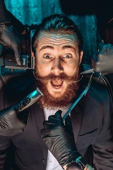 Portret van een charismatische aantrekkelijke man met een snor en baard, zittend op een fauteuil in een kapperszaak en verrast op zoek. rond zijn gezicht een schaar, scheermesjes. mannelijke sharm concept