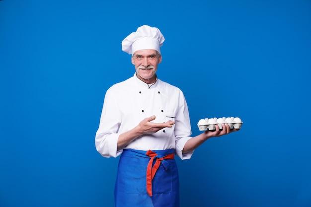 Portret van een charismatische bebaarde chef-kok die een mand met verse eieren vasthoudt terwijl hij tegen een blauwe muur poseert