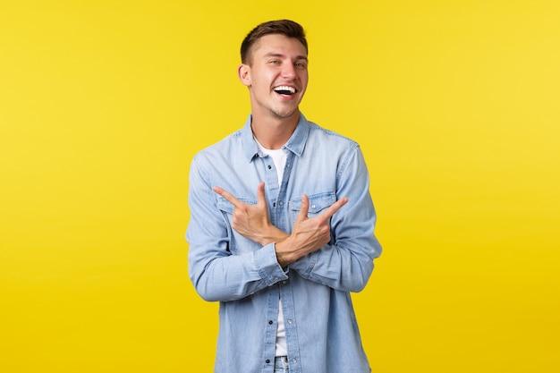 Portret van een charismatische knappe blonde man die blij lacht en met de vingers zijwaarts wijst, links en rechts varianten of producten laat zien, vrolijk over een gele achtergrond.