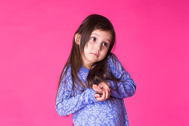 Portret van een charmant donkerbruin klein kindmeisje, dat op roze wordt geïsoleerd