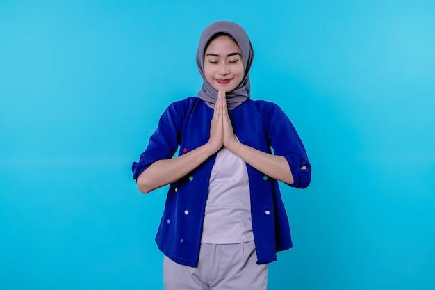 Portret van een charmant, dwaas, flirterig meisje in een hijab die hand in hand bidt in de buurt van de borst en breed glimlacht