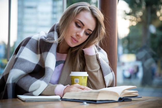 Portret van een charmant meisje dat een boek leest in café