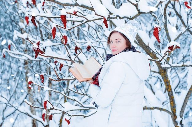 Portret van een charmant meisje dat een boek leest in het winterbos.