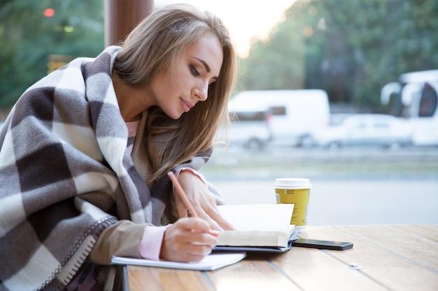 Portret van een charmant meisje dat huiswerk doet in café